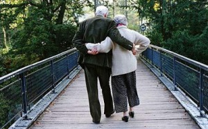 Elderly couple walking across footbridge Photo GETTY